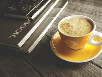 White and yellow ceramic cup filled of coffee beside book