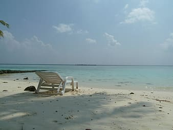 White metal lounger placed on white beach sand at daytime
