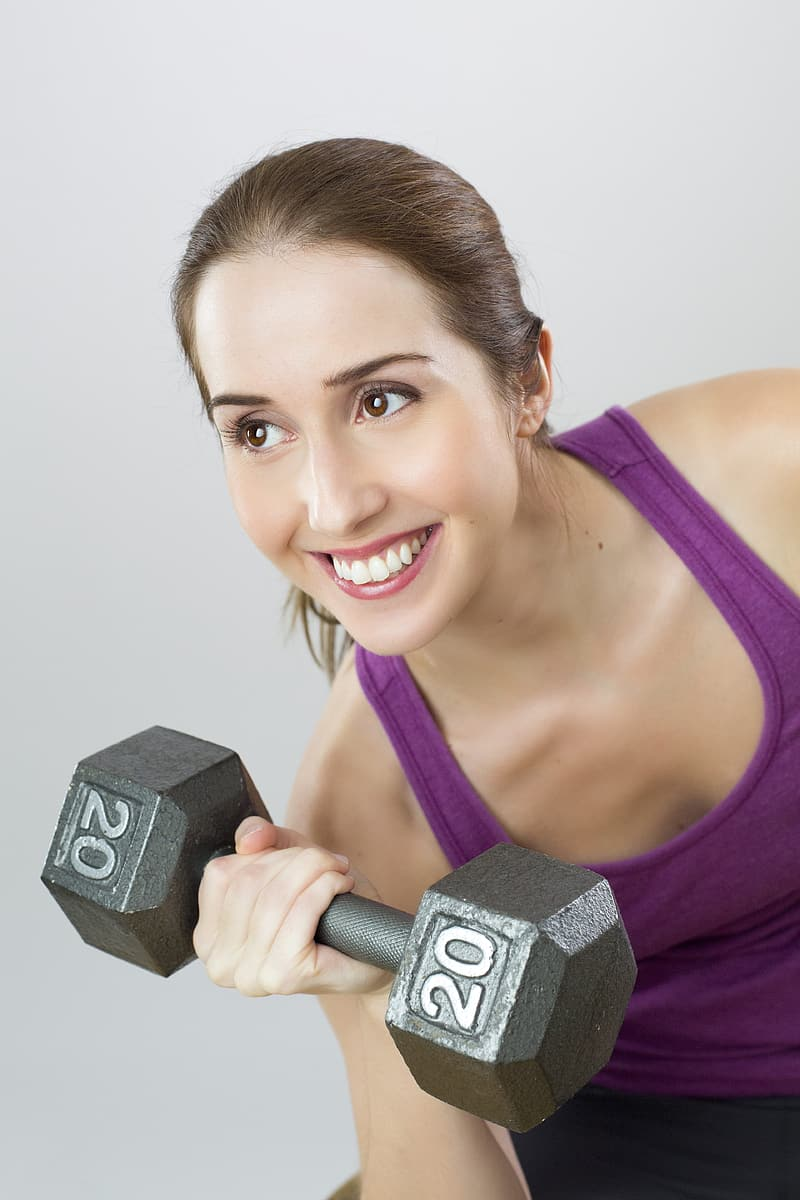 Woman in purple tank top lifting dumbbell