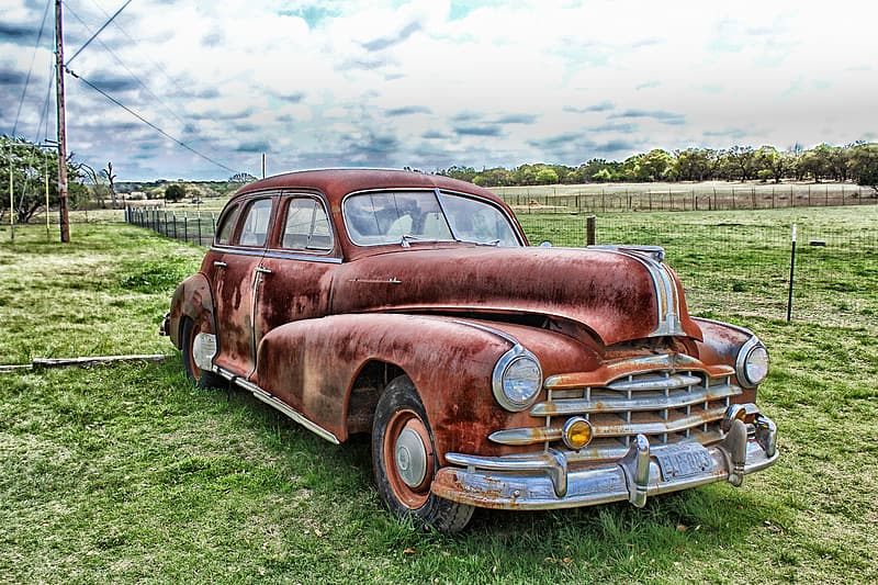 Rusted sedan parked on grass