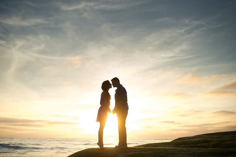 Silhouette of couple kissing on seashore during sunset