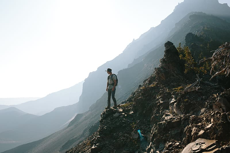 Man with backpack standing on rock