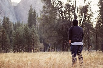 Man in black jacket standing on brown grass field during daytime