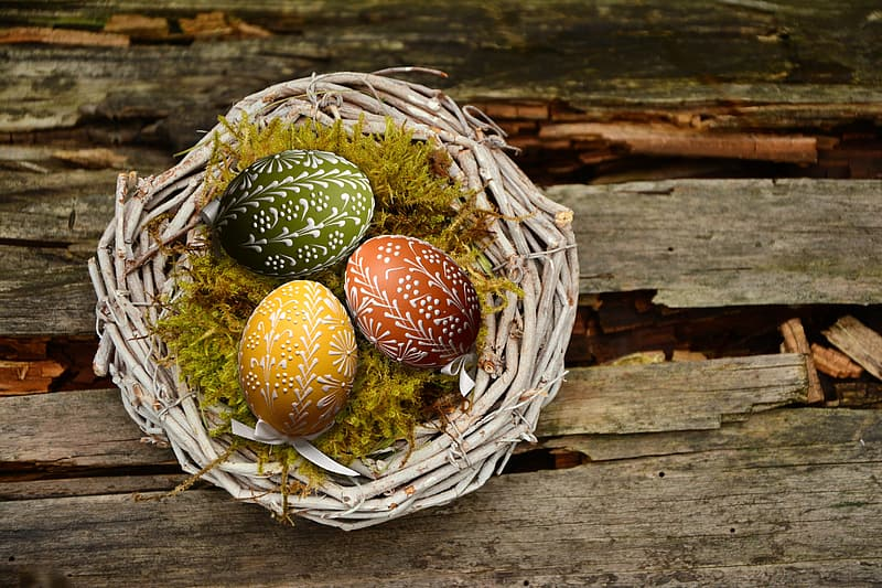 Yellow, green, and red easter eggs on brown bird nest