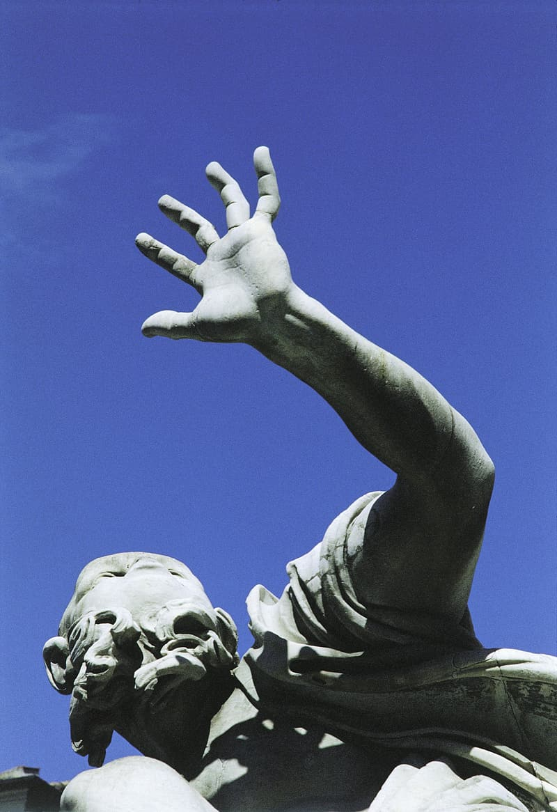 Low-angle photo of concrete male raising hand statue under blue sky