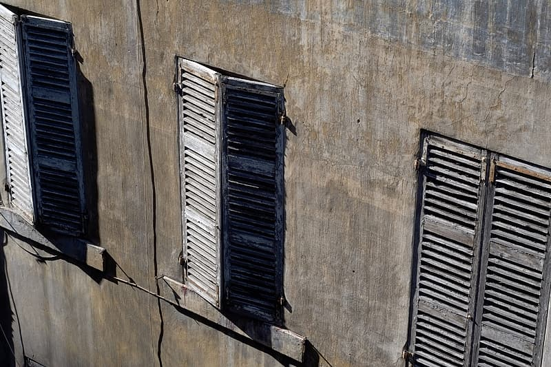 Blue wooden window on brown concrete wall