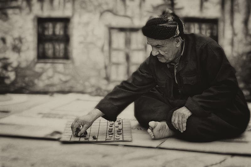 Grayscale photography of man playing checkers