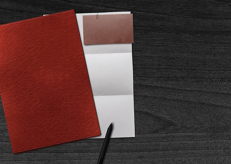 Red and white paper on black wooden table