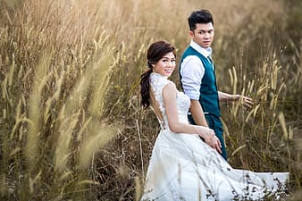Man in blue vest and woman in white dress on brown grass field during daytime