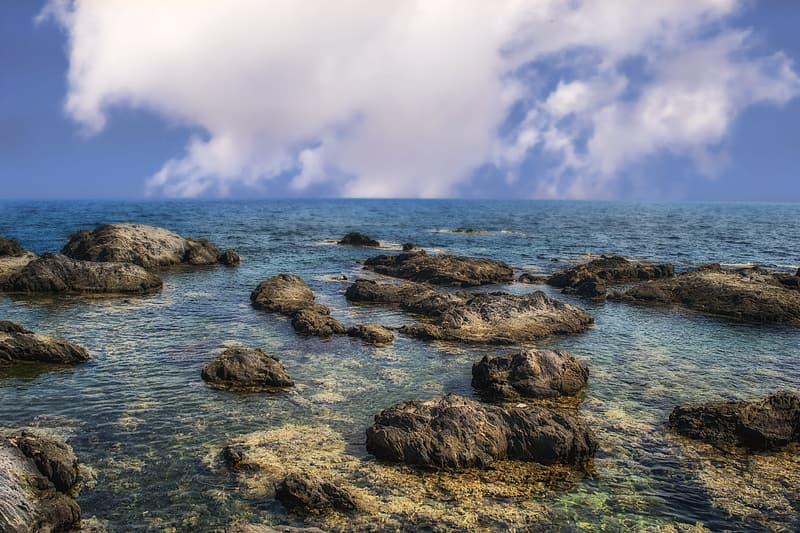 Brown rocks on sea shore under white clouds and blue sky during daytime
