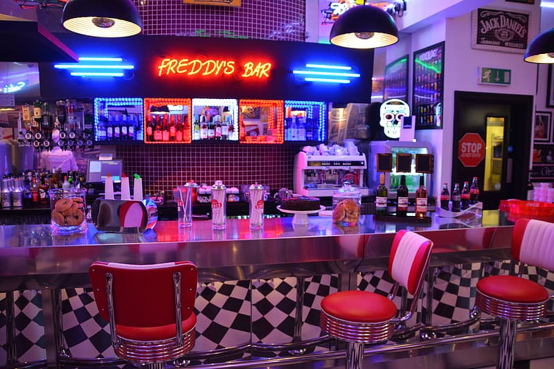 Freddy's Bar with neon lights turned on and red stools