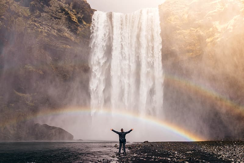 Person standing in front of waterfall during daytime