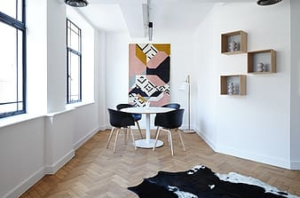 Round white pedestal table with four black chairs on brown surface