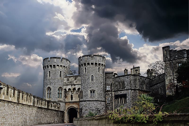 Gray concrete castle under black and blue cloudy sky
