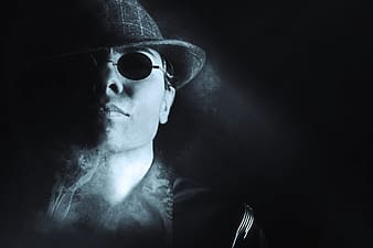 Man in round hat with smoke and sunglasses