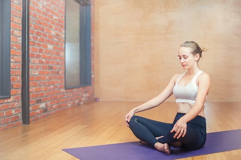Woman wearing blue tight pants while doing yoga