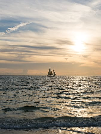 Sailing yacht in the middle of ocean during sunset