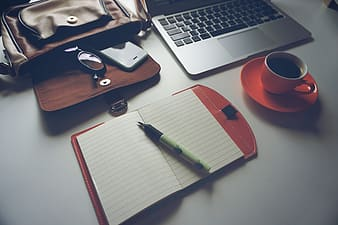 White pen on white notebook beside the orange ceramic coffee cup with saucer located on top of white table