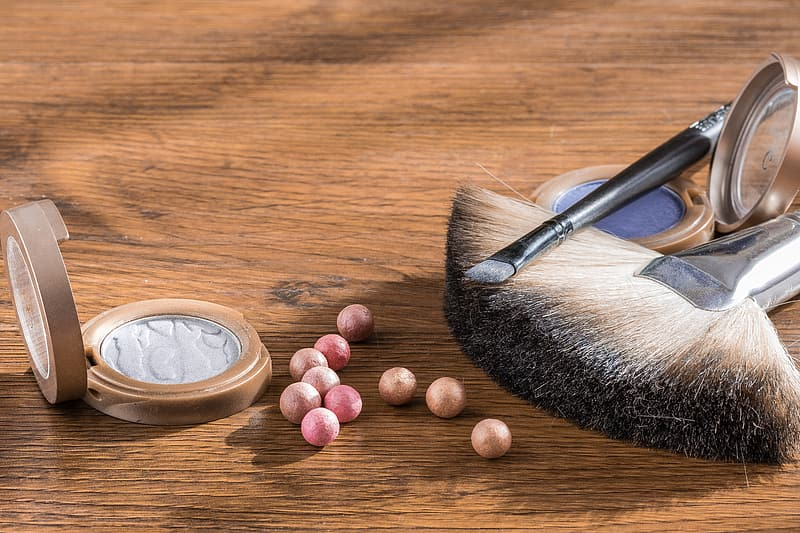 Two brown and black makeup brushes near two purple and gray makeup palettes on brown wooden surface