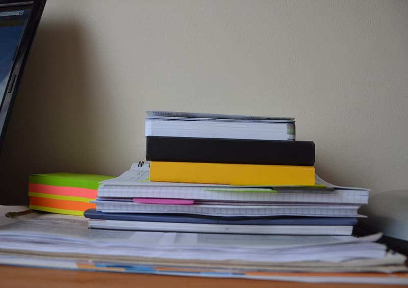 Pile of books on the desk with pink paper