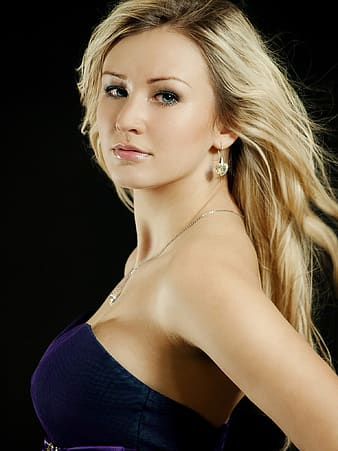 Photo of woman wearing blue sweetheart neckline dress with black background