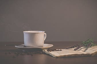 White ceramic cup of coffee on brown surface