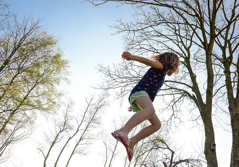 Girl jumping near trees