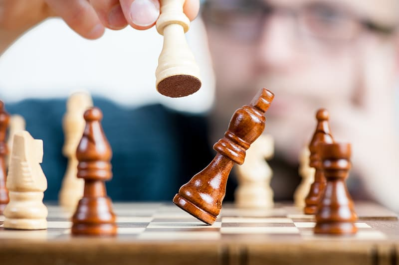 Person playing chess showing bishop chess piece