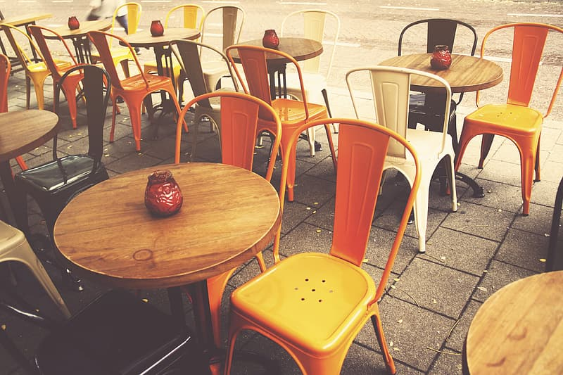 Round brown table beside two orange chairs