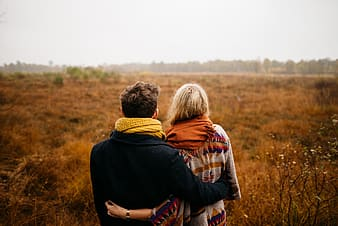 Man and woman standing on brown grass field during daytime