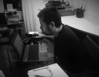 Grayscale photo of man sits facing laptop