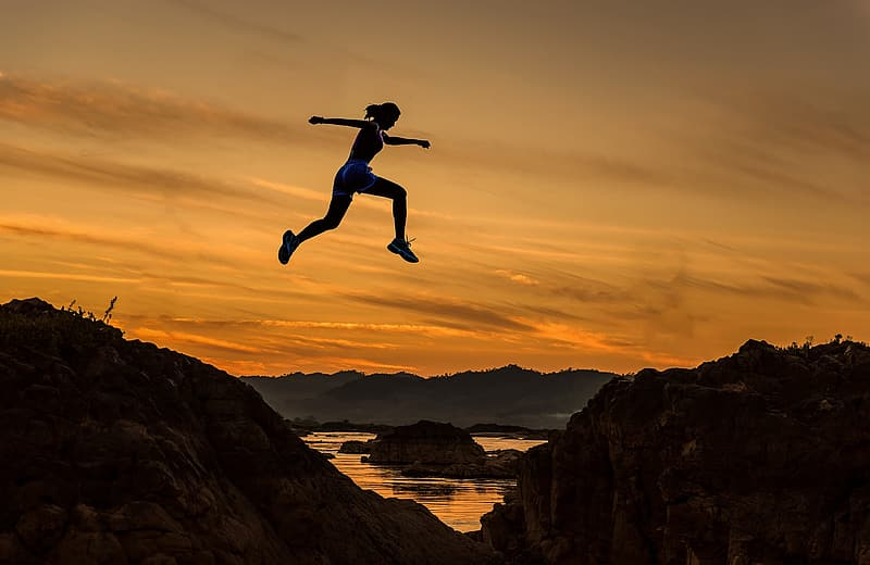 Silhouette of woman jump on the rock