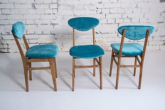 Blue fabric chairs with brown wooden frame near white wall