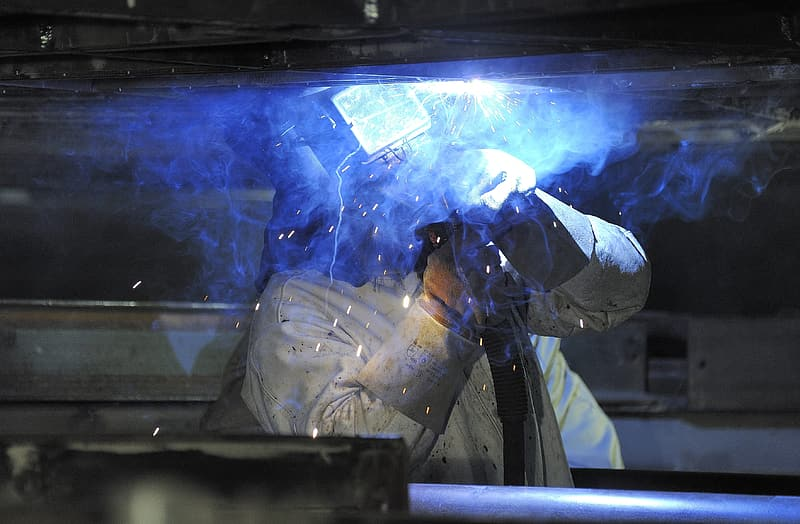 Person wearing white overalls welding iron