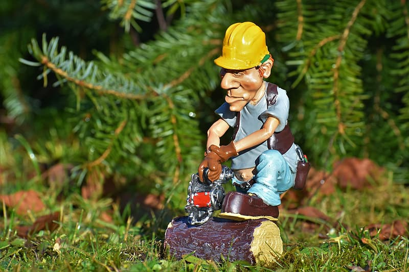 Man wearing blue shirt and holding chain saw figurine