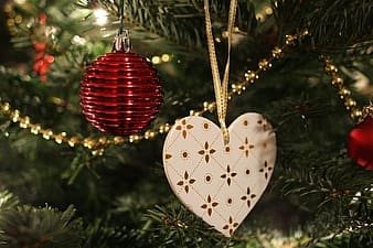 Red bauble and white heart ornament hanged on green Christmas tree