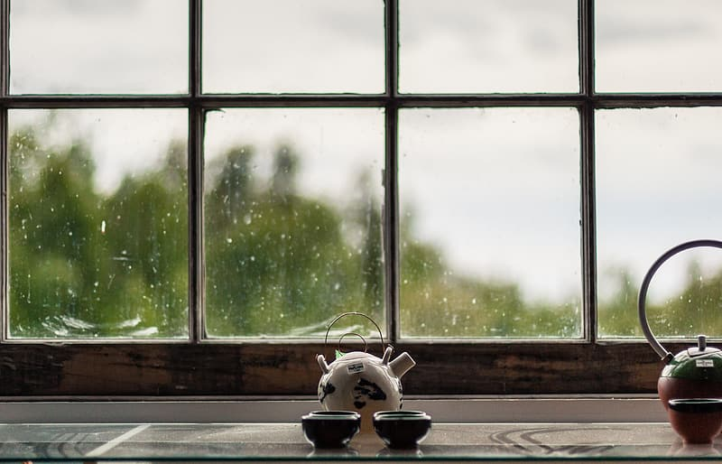 White ceramic teapot with two cups infront of the window