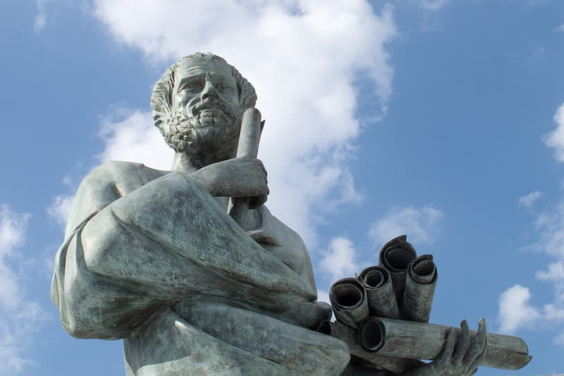 Low angle photo of man holding scroll grey statue during cloudy day