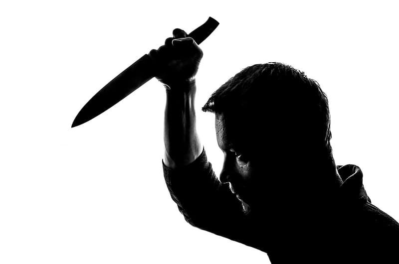 Man in black collared shirt holding knife