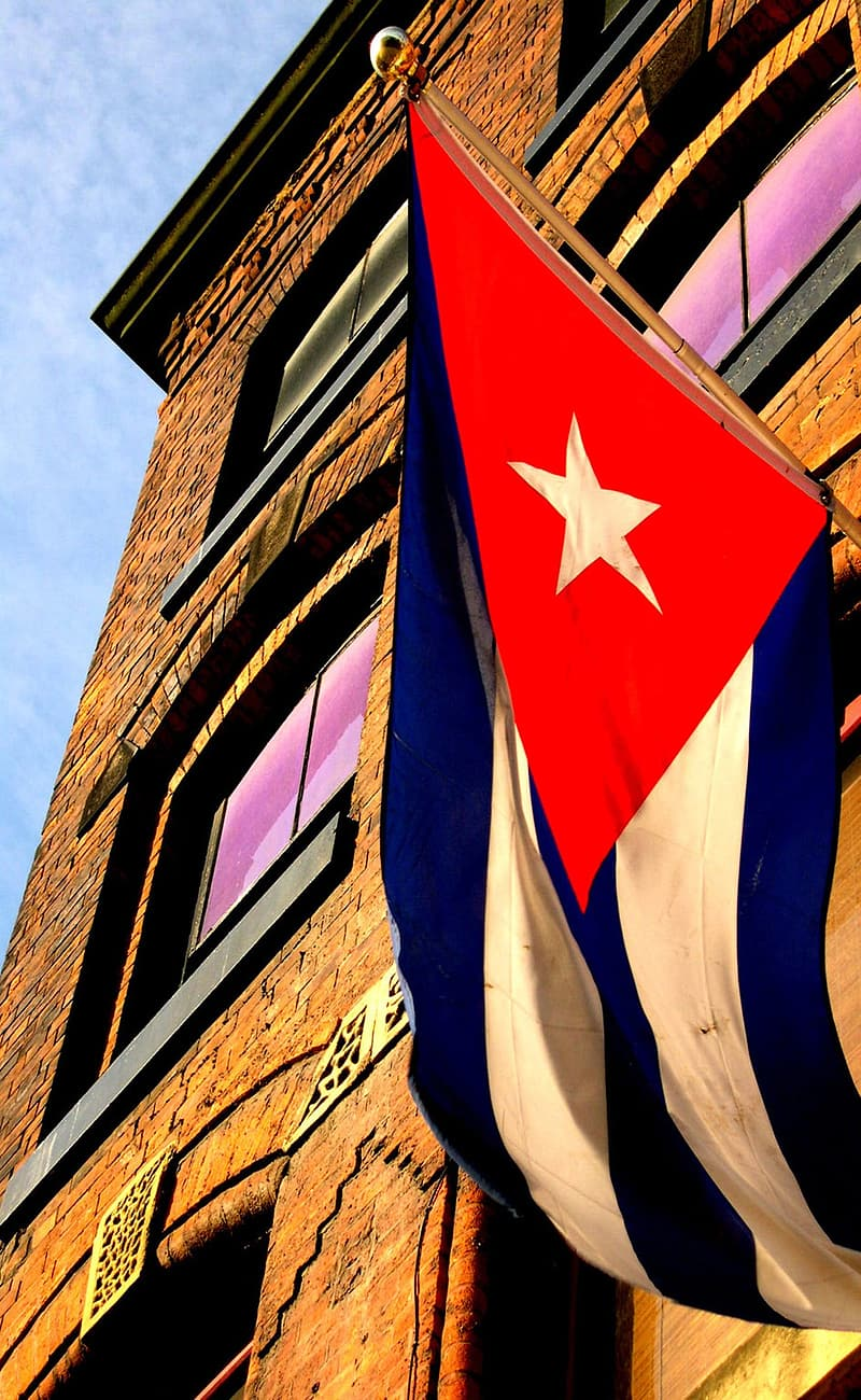 Low-angle photography of blue, white, and red star flag hanged on brown concrete building at daytime