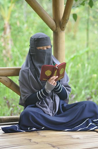 Woman in black hijab holding red smartphone
