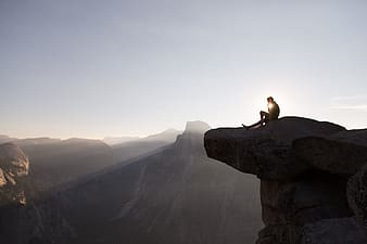 Man sitting on top of mountain during daytime