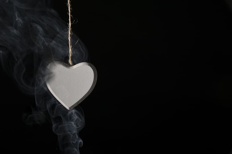 Silver-colored heart pendant with black smoke