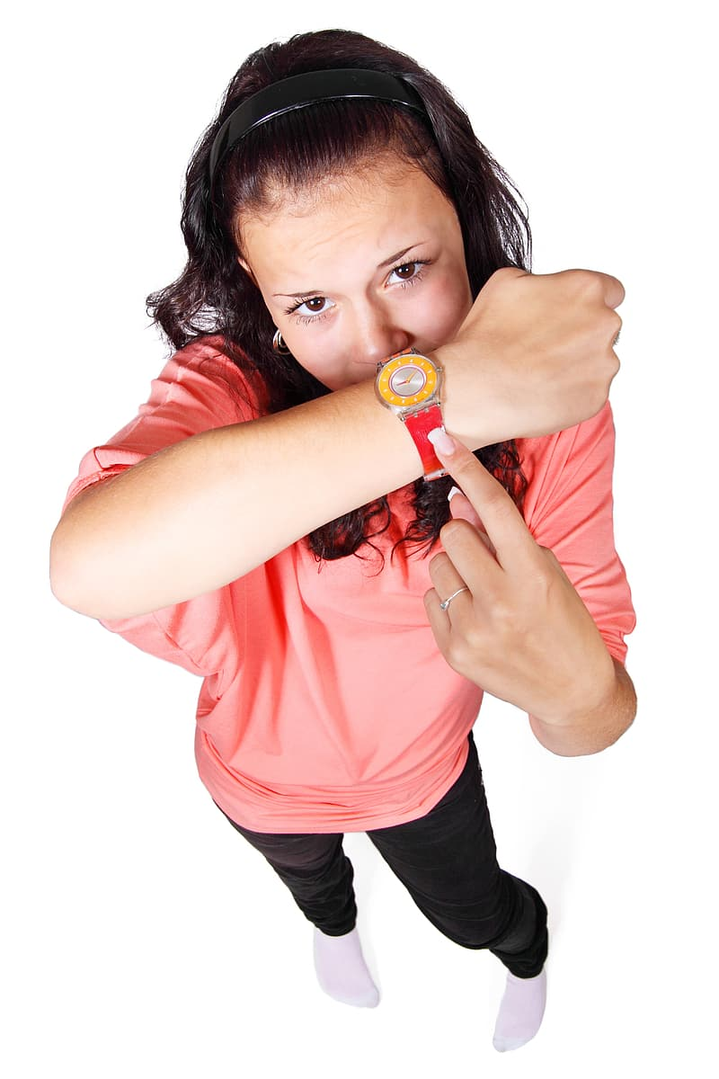 Woman wearing pink top and pointing her watch