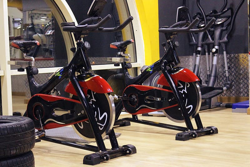 Two red-and-black stationary bikes near tires
