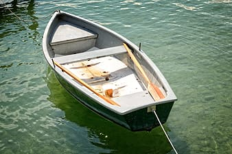 Green canoe boat on body of water during day time