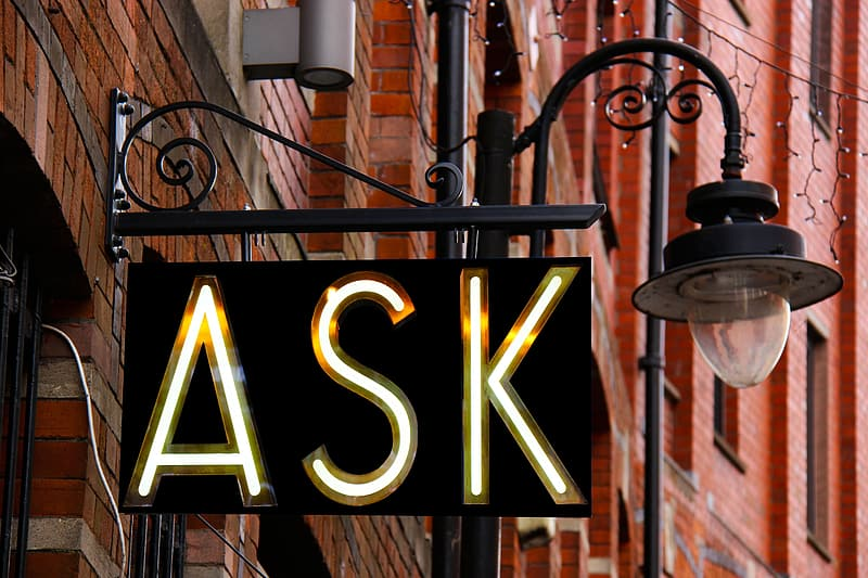 Photography of black metal sconce street light with ASK LED light signage