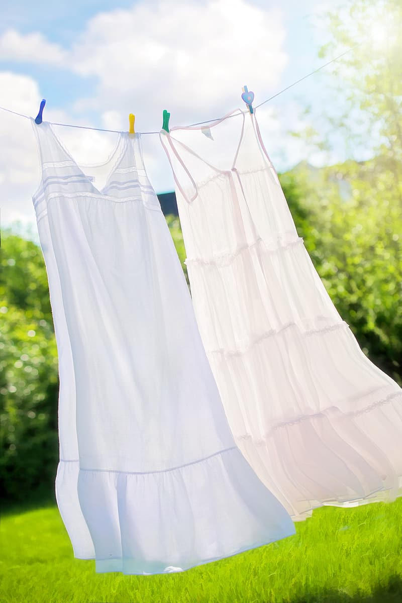 Two white long dresses hanged on white rope