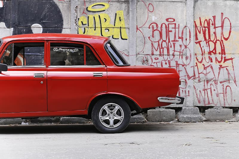 Red vehicle parking near white concrete wall