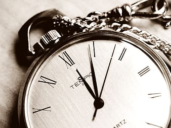 Grayscale photo of a pocket watch at 12:04:04